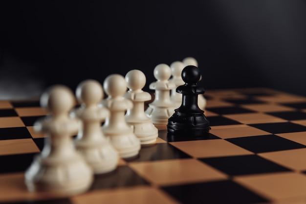 Concept de leadership, pion noir d'échecs se démarquant de la foule de blanc sur un échiquier