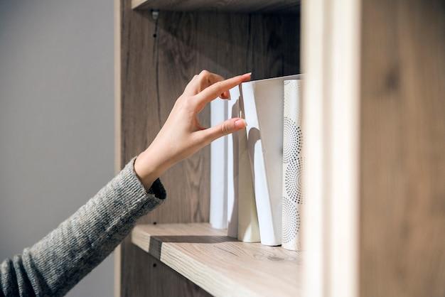 Concept de lecture. le ton vintage de la femme sélectionne un livre à partir d'une étagère. portrait d'une fille sérieuse dans la bibliothèque à la recherche d'un livre