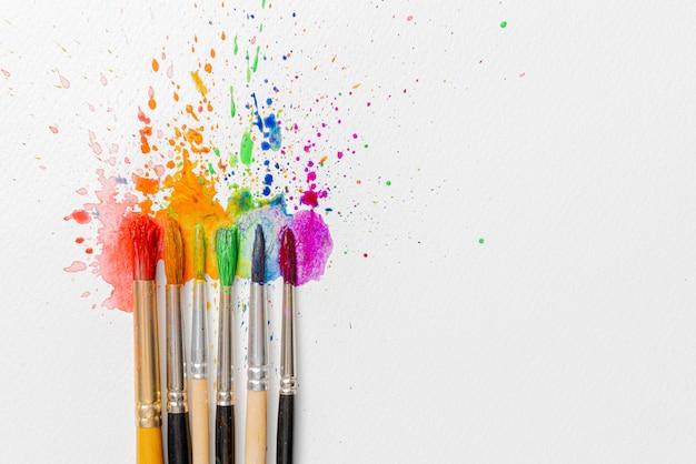 Concept lgbtq de couleurs réalisées à l'aide de peintures à l'aquarelle et de pinceaux de fleurs d'azalée sur une feuille de papier pour l'aquarelle