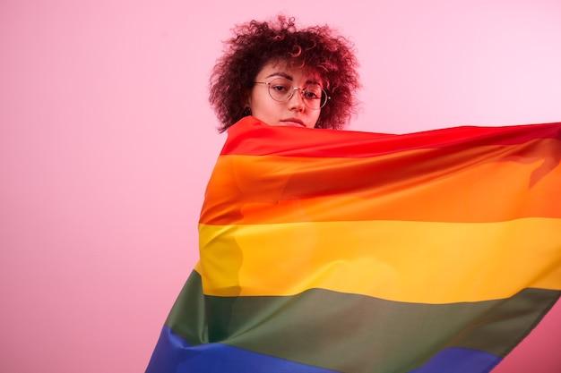 Concept lgbtq. fille caucasienne positive avec des cheveux bouclés afro tenant le drapeau arc-en-ciel isolé