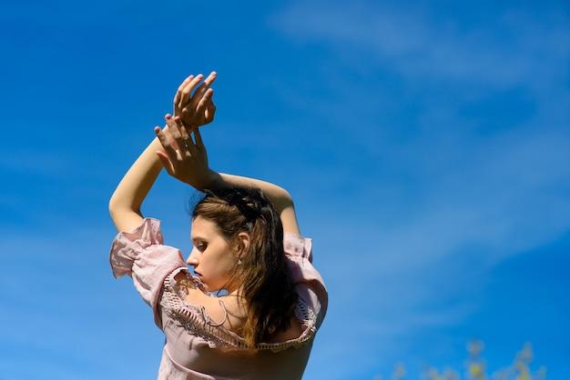 Concept de liberté de bonheur. femme heureuse souriante joyeuse avec les bras levés dansant, vacances d'été.