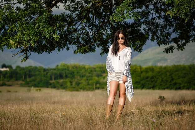 Concept de liberté d'esprit. jolie jeune femme marche dans le champ. elle a hâte avec un léger sourire.