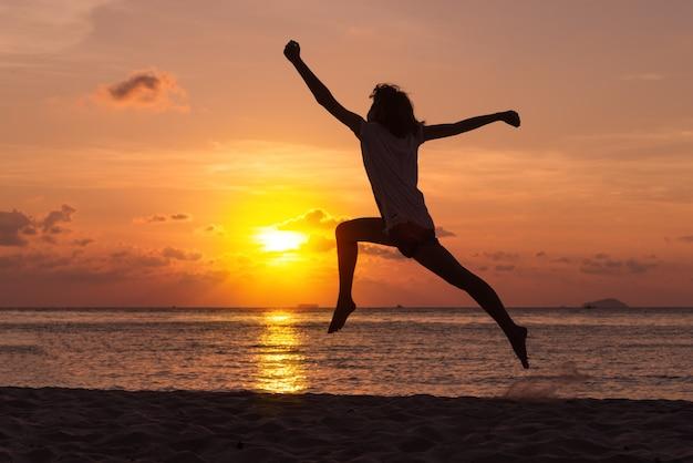 Concept de liberté avec un jeune adolescent heureux et saut sur la plage