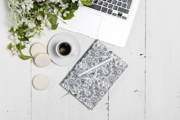 Concept de lieu de travail féminin moderne. ordinateur portable, café, belles fleurs de pommier sur le tableau blanc, vue de dessus