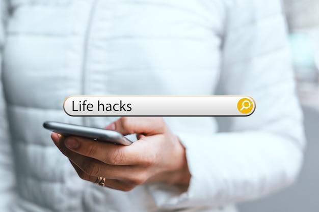Concept life hacks dans la barre de recherche sur le fond d'une femme avec téléphone.