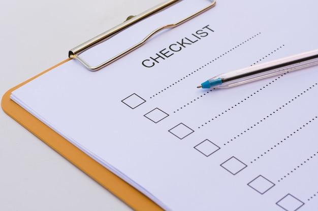 Concept de liste de contrôle - liste de contrôle, papier et un stylo avec le mot de la liste de contrôle sur la table en bois