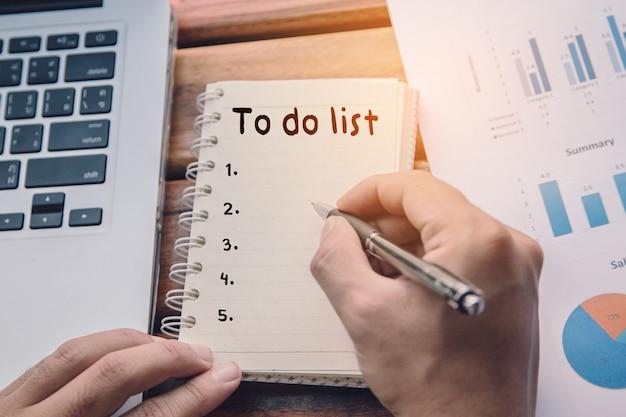 Concept de liste de tâches. mains d'homme écrivant sur un cahier
