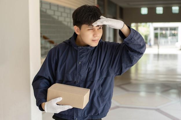 Concept de livraison de colis le facteur dans des gants en caoutchouc blanc et un manteau bleu foncé léger à la recherche du destinataire pour remettre la boîte à colis.