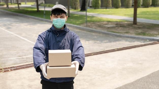 Concept de livraison de colis le jeune expéditeur soulevant deux boîtes de colis et se tenant au milieu d'une rue étroite pour chercher un bâtiment où il déposera ces deux colis.