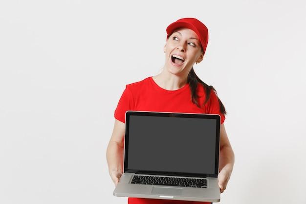 Concept de livraison. femme au bonnet rouge, t-shirt isolé sur fond blanc. femme caucasienne professionnelle travaillant comme coursier tenant un ordinateur pc avec un écran vide vide pour copier l'espace pour la publicité.