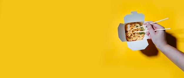 Le concept de livraison de nourriture sur fond jaune nouilles dans des boîtes