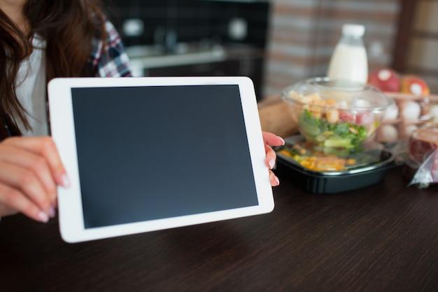 Concept de livraison de nourriture. une jeune femme commande de la nourriture à l'aide d'un ordinateur portable à la maison. sur la table, il y a du lait, des salades dans des boîtes, de la viande, de la nourriture, des fruits, des œufs, du pain.