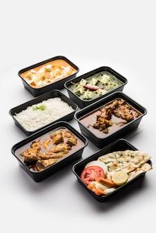 Concept de livraison de nourriture en ligne beurre de paneer indien masala et palak paneer, curry de mouton et de poulet avec roti et riz dans des récipients en plastique, aliments comme le poulet au beurre, le poulet