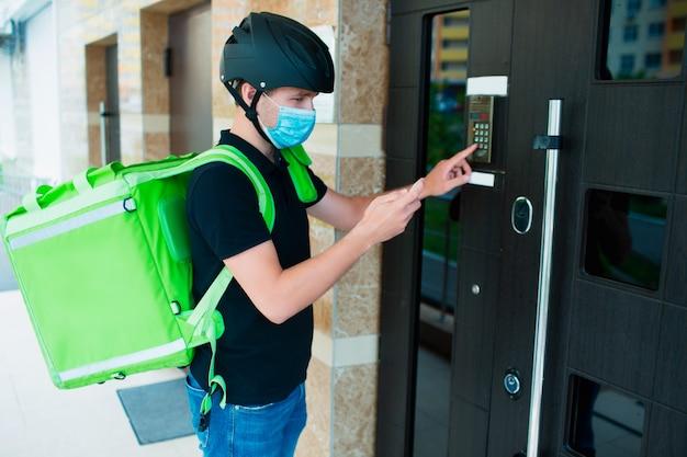 Concept de livraison de nourriture. livreur de nourriture sonnant sur l'interphone. il porte un masque médical