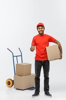Concept de livraison - portrait de handsome african american delivery man ou de messager poussant un camion à main avec pile de boîtes. isolé sur fond de studio gris. espace de copie.