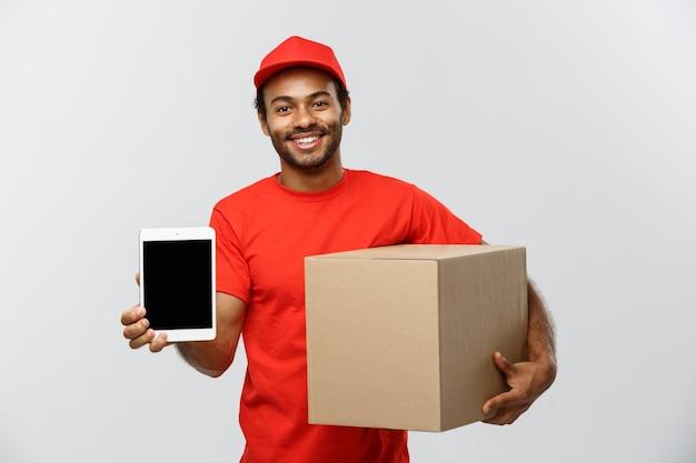 Concept de livraison - portrait de handsome african american delivery man ou de messagerie avec boîte montrant tablette sur vous pour vérifier la commande. isolé sur fond de studio gris. espace de copie.