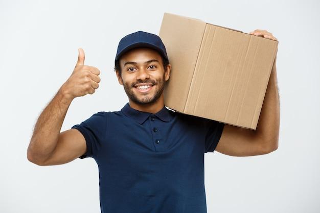 Concept de livraison - portrait de l'homme de livraison happy african american qui pointe la main pour présenter un coffret. isolé sur fond de studio gris. espace de copie.