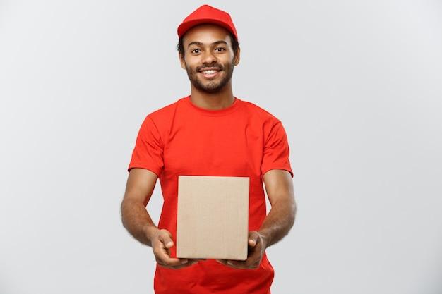 Concept de livraison - portrait de l'homme de livraison happy african american en tissu rouge tenant un paquet de boîte. isolé sur fond de studio gris. espace de copie.