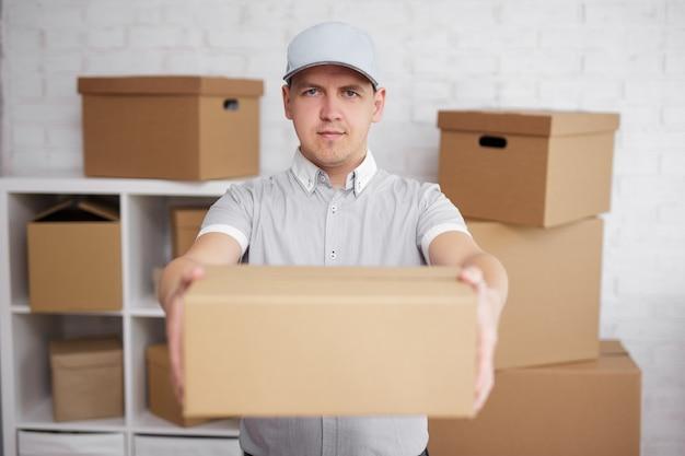 Concept de livraison postale - livreur donnant une boîte dans un entrepôt ou un bureau de poste