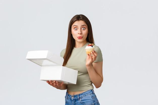 Concept de livraison, de style de vie et de nourriture. femme heureuse excitée à la surprise de recevoir des cupcakes préférés d'une petite pâtisserie locale, comme manger des bonbons, faire une commande en ligne, fond blanc