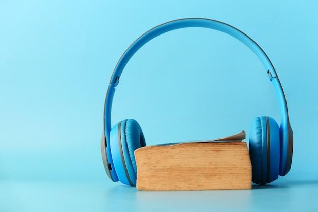 Concept de livre audio. casque et bloc-notes sur fond blanc.