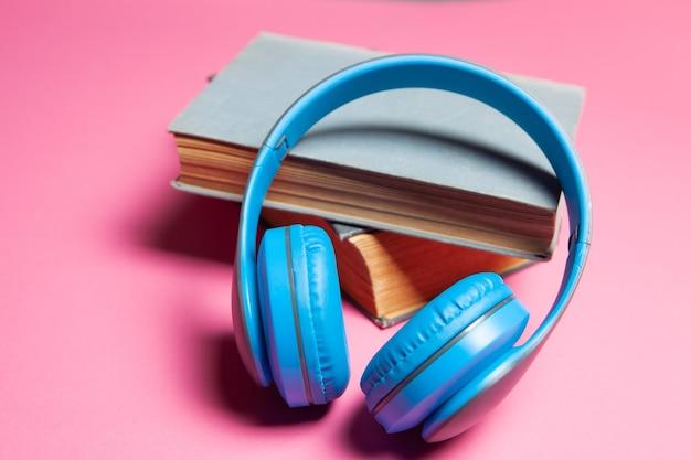 Concept de livre audio. livres et écouteurs sur fond rose