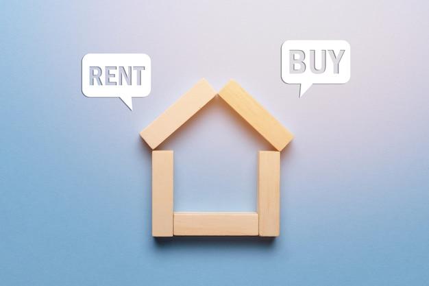 Concept de location ou d'achat de maison immobilière faite de blocs de bois avec des icônes.