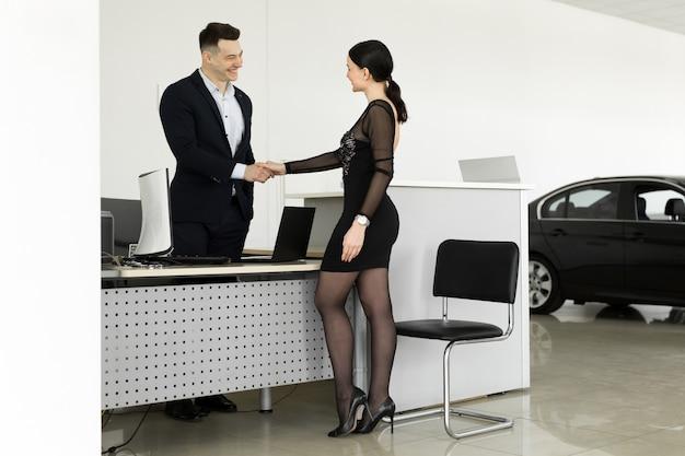 Concept de location de voiture et d'assurance, jeune vendeur recevant de l'argent et donnant la clé de la voiture au client après la signature du contrat d'accord avec une bonne affaire approuvée pour la location ou l'achat.