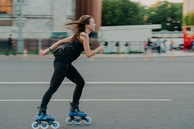 Concept de loisirs actifs. plan complet d'une jeune femme mince faisant du roller le long de l'asphalte dans la rue aime la vitesse passe du temps libre sur des poses de passe-temps préférées à l'extérieur respire l'air frais roller