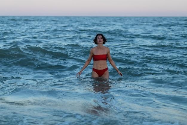 Concept de loisirs d'été. belle jeune femme sexy avec un corps mince formé en forme portant des poses de bikini de maillot de bain rouge sur une plage de sable. mannequin femme près de la mer.