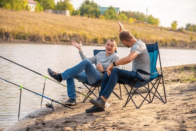 Concept de loisirs et de personnes. amis heureux avec des cannes à pêche sur la jetée au bord du lac.