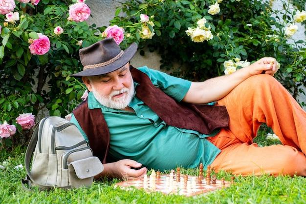 Concept de loisirs senior de printemps. vieil homme au printemps jardin avec échecs. passe-temps. bonne vieillesse.
