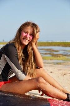 Concept de loisirs, de sport et de style de vie. fille joyeuse aime le surf, se repose après le voyage