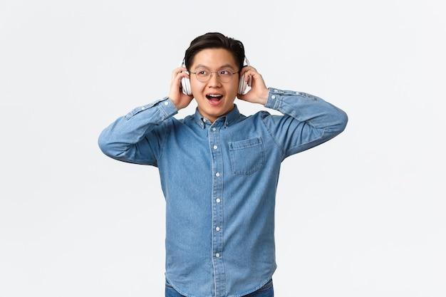 Concept de loisirs et de technologie de style de vie souriant un gars asiatique étonné dans des verres essayant de nouvelles hea sans fil ...