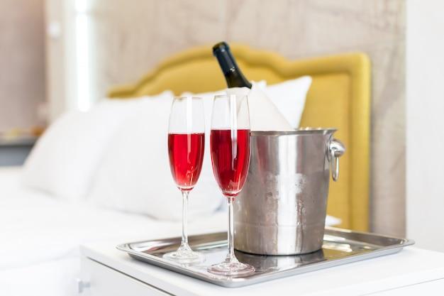 Concept de lune de miel. seau à champagne près du lit dans une chambre d'hôtel