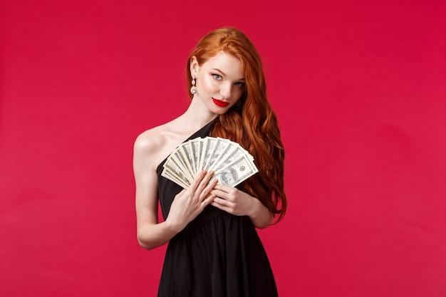 Concept de luxe, de beauté et d'argent. portrait de jeune femme rousse sensuelle, jolie et séduisante en robe élégante noire, laissant entendre que vous pouvez obtenir cet argent en espèces si vous placez une bonne mise, souriant audacieux