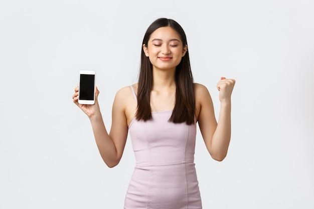 Concept de luxe femmes, fête et vacances. satisfait de femme asiatique souriante sentant le goût sucré de