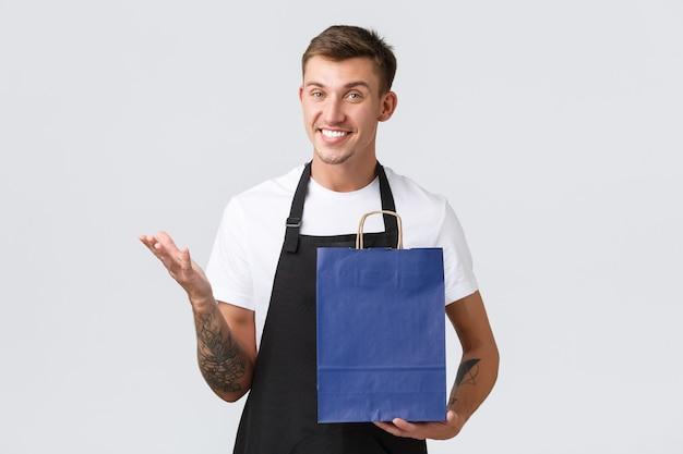 Concept de magasin de détail, de shopping et d'employés. vendeur blond souriant charismatique dans la boutique, parlant au client, emballant le produit dans des sacs écologiques, debout sur fond blanc à l'aspect amical