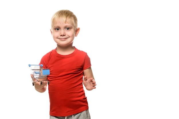Concept de magasinage. blond mignon petit garçon souriant en t-shirt rouge tenant un petit caddie en métal. isoler sur blanc
