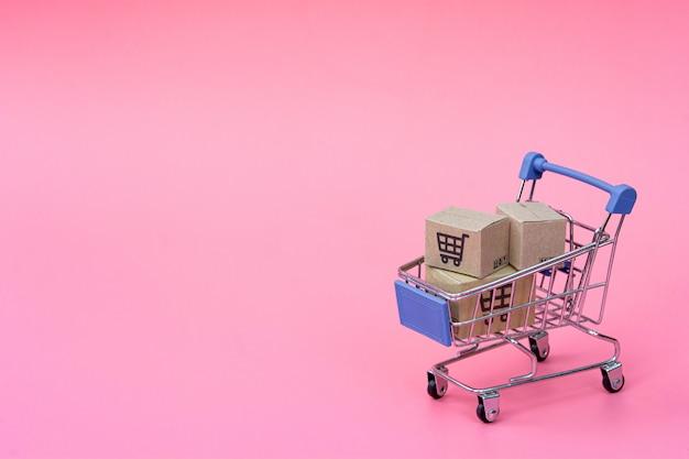 Concept de magasinage: cartons ou boîtes de papier dans le panier d'achat bleu sur rose. les consommateurs qui achètent en ligne peuvent faire leurs achats depuis leur domicile et leur service de livraison. avec copie espace