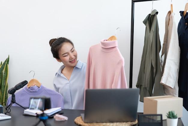 Concept de magasinage en direct un appareil photo numérique enregistrant une vidéo d'une vendeuse et se connectant à un appareil pour diffuser un magasinage en direct.