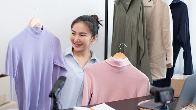 Concept de magasinage en direct un appareil photo numérique enregistrant une vidéo d'une vendeuse