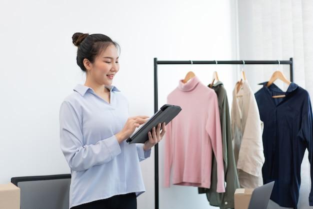 Concept de magasinage en direct une commerçante téléchargeant des informations et des photos des marchandises sur sa boutique en ligne.