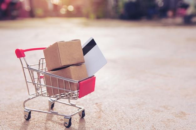 Concept de magasinage en ligne: boîtes de carton ou de papier et carte de crédit dans le panier. en ligne