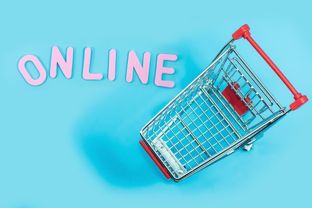 Concept de magasinage en ligne avec chariot sur bleu pour le fond