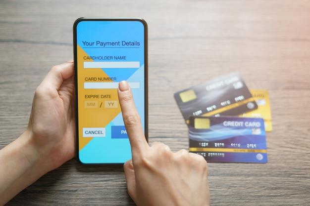 Concept de magasinage en ligne: mains de femme tenant une carte de crédit et utilisant les achats en ligne par carte de crédit (faux écran)