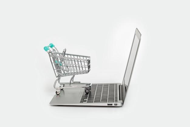 Concept de magasinage en ligne avec ordinateur portable et panier isolé sur fond blanc avec espace copie, gros plan. commerce électronique