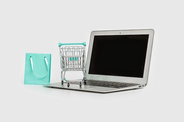 Concept de magasinage en ligne avec ordinateur portable, sac à provisions et chariot isolé sur blanc, espace copie
