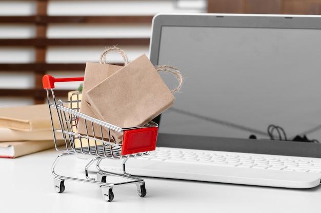 Concept de magasinage en ligne. panier, ordinateur portable sur le bureau