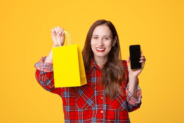 Concept de magasinage en ligne, services bancaires en ligne, femme souriante portant une chemise à carreaux montrant mobile